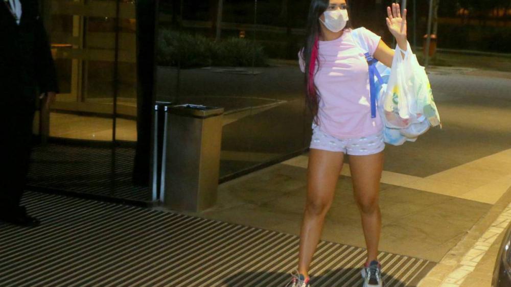 Eliminada, Flay chega ao hotel de máscara mas tira para falar com fãs